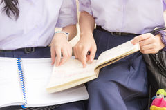 Body and hands of Asian Thai high schoolgirls student couple reading. Body and hands of cute Asian Thai high schoolgirls student couple in school uniform sitting stock photos