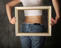 Body image. Woman's torso with frame held in front of waist stock image