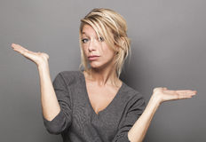 Body language concept for dubious 20s blond woman. Body language concept - dubious 20s blond woman weighting a product on both palms of her hands for value or Stock Photos
