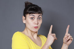 Body language concept for funny woman showing something. Body language concept - funny 20s woman showing a product or something up with two fingers and focused royalty free stock photo