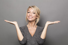 Body language concept for satisfied 20s blond woman. Body language concept - satisfied 20s blond woman balancing something on both palms of her hands for equal Stock Photos