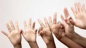 Many raised children`s expressive hands in a row. Body language in relationships of friends and companies.. many raised children`s expressive hands in a row stock photos