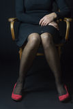 Body language - sitting woman. Woman in red pumps and black stockings is sitting with parallel legs on an old chair. This position reflects Royalty Free Stock Photo
