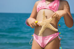 Body of little girl with starfish on beach Royalty Free Stock Photos