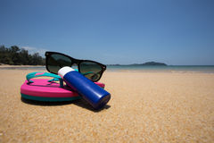 Body lotion, pink flip flops and Sunglasses on the beach.  Stock Image
