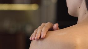 Body lotion on skin. Sensual woman spreading body lotion on tanned skin close-up. Female hand cream applying after sunbathing stock video footage