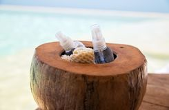 Body lotion spray in coconut shell at beach spa Royalty Free Stock Photos