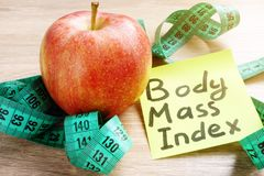 Body Mass Index BMI written on a memo stick and apple. royalty free stock photography