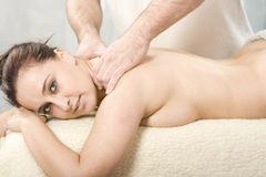 Body massage. Relaxing nice lady having a massage treatement Stock Images