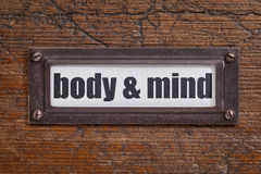 Body and mind  label. Body and mind  - file cabinet label, bronze holder against grunge and scratched wood Stock Photos