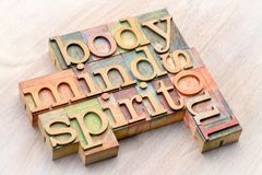 Body, mind, spirit and soul word abstract in wood type. Body, mind, spirit and soul word abstract in letterpress wood type stained with color inks against Royalty Free Stock Images