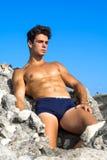 Georgian boy while sunbathing on the rocks. Man a bitch in rome Stock Image