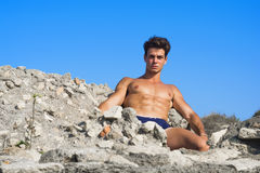 Body model man. Man lying on a rock by the sea Royalty Free Stock Images