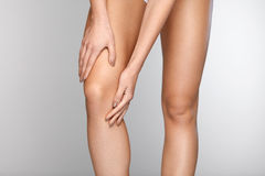Body Pain. Close-up Of Beautiful Female Body With Pain In Knees. Closeup Of Girl Feeling Joint Pain In Leg. Woman Hands Touching And Massaging Painful Knee Royalty Free Stock Image