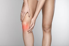 Body Pain. Close-up Of Beautiful Female Body With Pain In Knees. Closeup Of Girl Feeling Joint Pain In Leg. Woman Hands Touching And Massaging Painful Knee Royalty Free Stock Photography