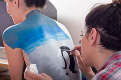 Body-painting on girl's back (1). Makeup artist body-painting on girl's back (1 Royalty Free Stock Photo