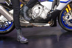 Body part of leg of man sitting a motorcycle Stock Photo