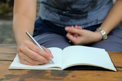Body part. Woman writing on note book . Body part. In the morning a lady sitting and writing on note book  in public park Stock Photography