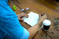 Body part. a man writing on note book . Body part. In the morning a man sitting and writing on note book  in public park Stock Images