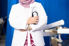 Body part of muslim Hijab female dentist holding stethoscope standing in front of dentist chair in her own clinic stock image