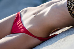 Body part of navel ring on her flat belly Royalty Free Stock Image