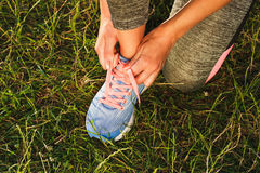 Body part: Sportswoman ties shoelaces on her shoes Stock Images