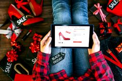 Body part of woman female adult buying new red high heels on internet online store shop with tablet during black friday holiday royalty free stock images
