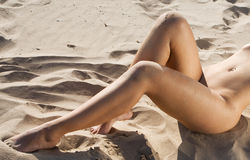 Body parts of a nude woman on a beach Stock Image