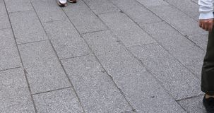 Body parts of walking people at the stone paved road in Asakusa