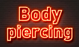 Body piercing neon sign on brick wall background. Stock Images