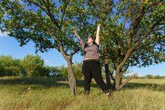 Overweight woman rising hands towards the sky royalty free stock photo