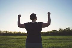 Overweight woman celebrating rising hands to sky. Body positive, freedom, high self esteem, confidence, happiness, inspiration, success, positive affirmation stock image