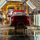The body of the red car on the production line. Plant vehicles or car repair shop. Auto tuning studio. Square frame. The body of the red car on the production stock photos