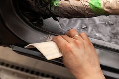 The body repairman grinds the white car`s frame with purple emery paper in preparation for painting after applying putty in a stock images