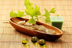 Body scrub. Bowl of body scrub with ginko leaves - beauty treatment Royalty Free Stock Photos