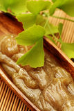 Body scrub. Bowl of body scrub with ginko leaves - beauty treatment Royalty Free Stock Images