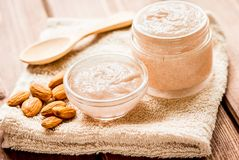 Body scrub with almonds for body care on wooden table background. Organic body scrub with almonds for body care concept on wooden table background royalty free stock photo