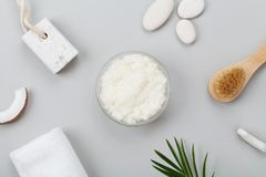 Body scrub of coconut oil, sugar and shavings in glass jar from above. Homemade cosmetic for peeling and spa care. Flat lay. Body scrub of coconut oil, sugar Royalty Free Stock Photography