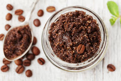 Body scrub of ground coffee, sugar and coconut oil in glass jar on white rustic table, homemade cosmetic for peeling and spa Stock Images