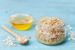 Body scrub of oatmeal, sugar, honey and oil in glass jar on blue rustic table, homemade cosmetic for peeling and spa Stock Image