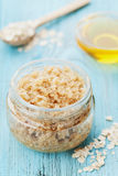 Body scrub of oatmeal, sugar, honey and oil in glass jar on blue rustic table, homemade cosmetic for peeling and spa Royalty Free Stock Images