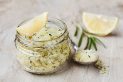 Body scrub of sea salt with lemon, rosemary and olive oil in glass jar on stone table Royalty Free Stock Images