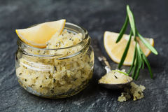 Body scrub of sea salt with lemon, rosemary and olive oil in glass jar on stone table Royalty Free Stock Photography