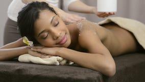 Body scrub at spa. Spa therapist applying scrub salt on young woman back at salon spa. Beautiful young woman scrubbing body. Body scrub at spa center. Beautiful stock footage