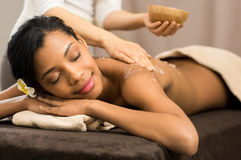 Body scrub at spa. Spa therapist applying scrub salt on young women back at salon  spa Stock Images