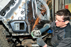 In the body shop. Proffesional car body repair, grinding welds Stock Photos