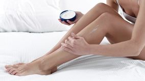 Body Skin Care. Woman Applying Body Cream On Leg Skin At Bedroom