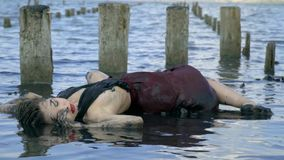 Body slender blonde smeared in mud and wet dress lies in the estuary near the wooden posts from the destroyed salt pool