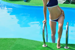 The body is slender young woman, goes the stairs to the pool. Royalty Free Stock Images