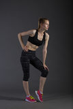 Body of slim female in activewear doing posin on gray low key, perfect blonde Royalty Free Stock Photos